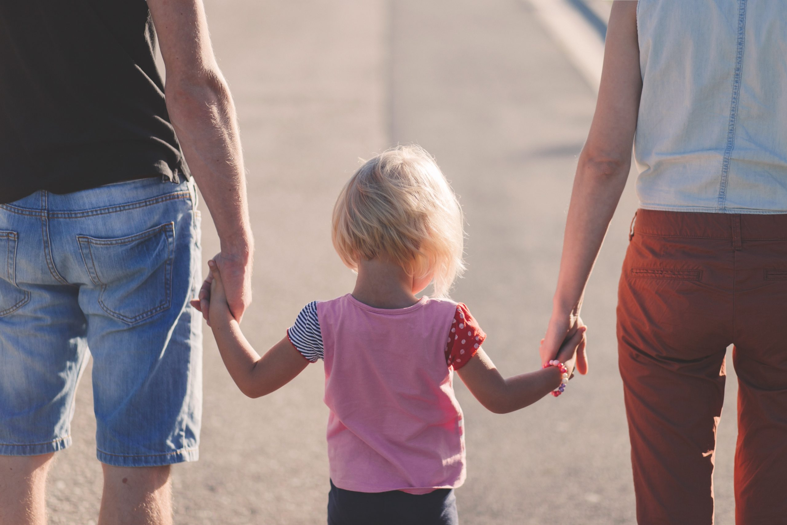 baby holding hands with adults