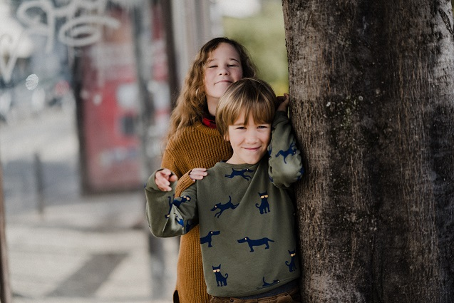 teen girl with arm around younger brother leaning against a wall - positive effects of divorce on kids